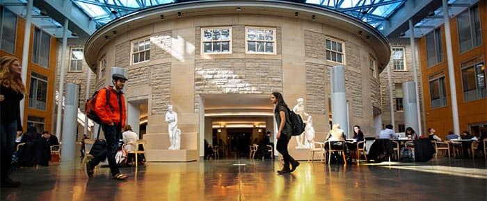 Several students walk through the Klarman Hall atrium